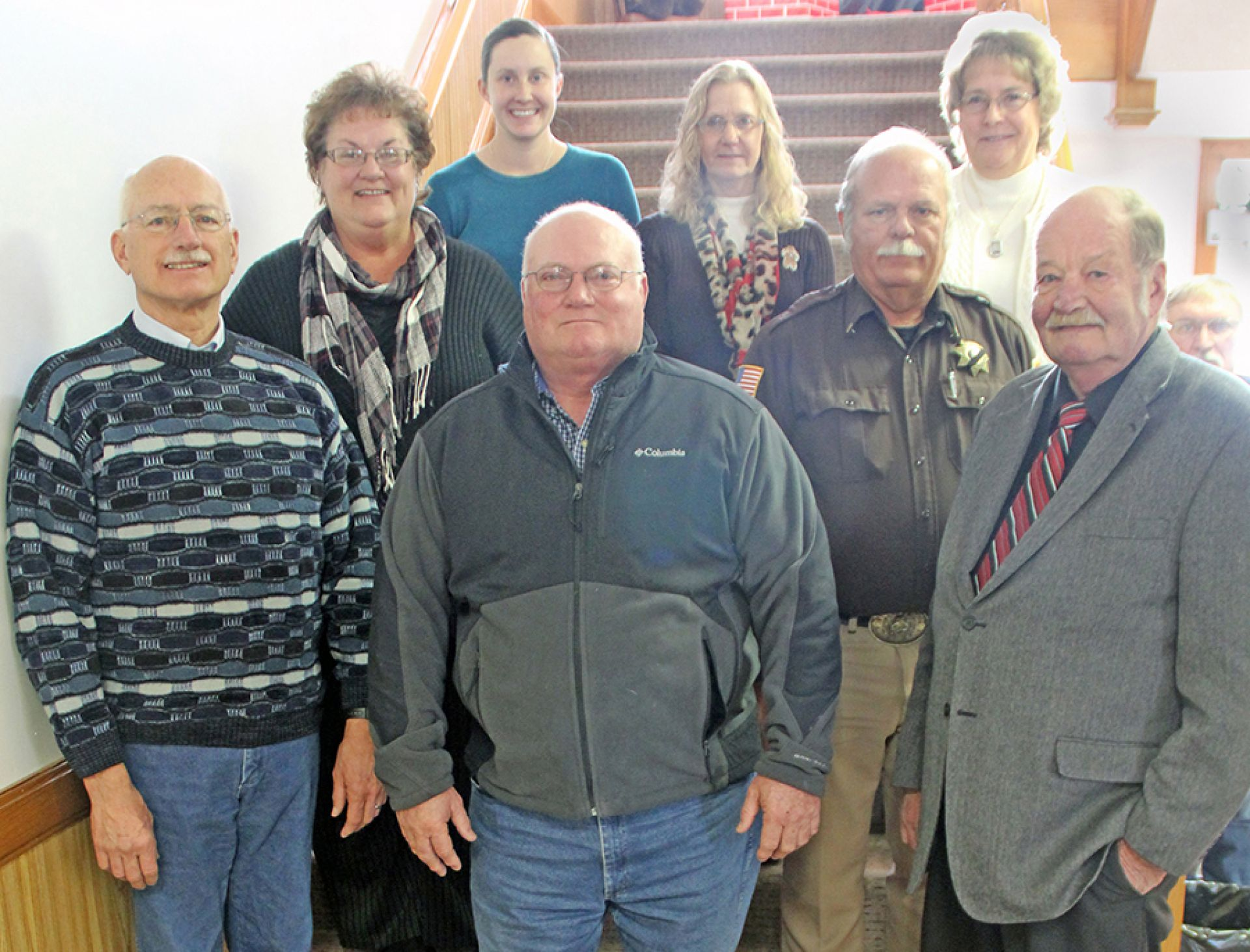Chairperson Dan Kling stands with his fellow commissioners and county workers on his last day. Front from left to right: James Krotz, Dan Kling, Jack Andersen Middle: Sid Coburn, Terry Robbins, Dwaine Sones Back: Amanda Lane, Carol Stouffer, and Peg Sones.