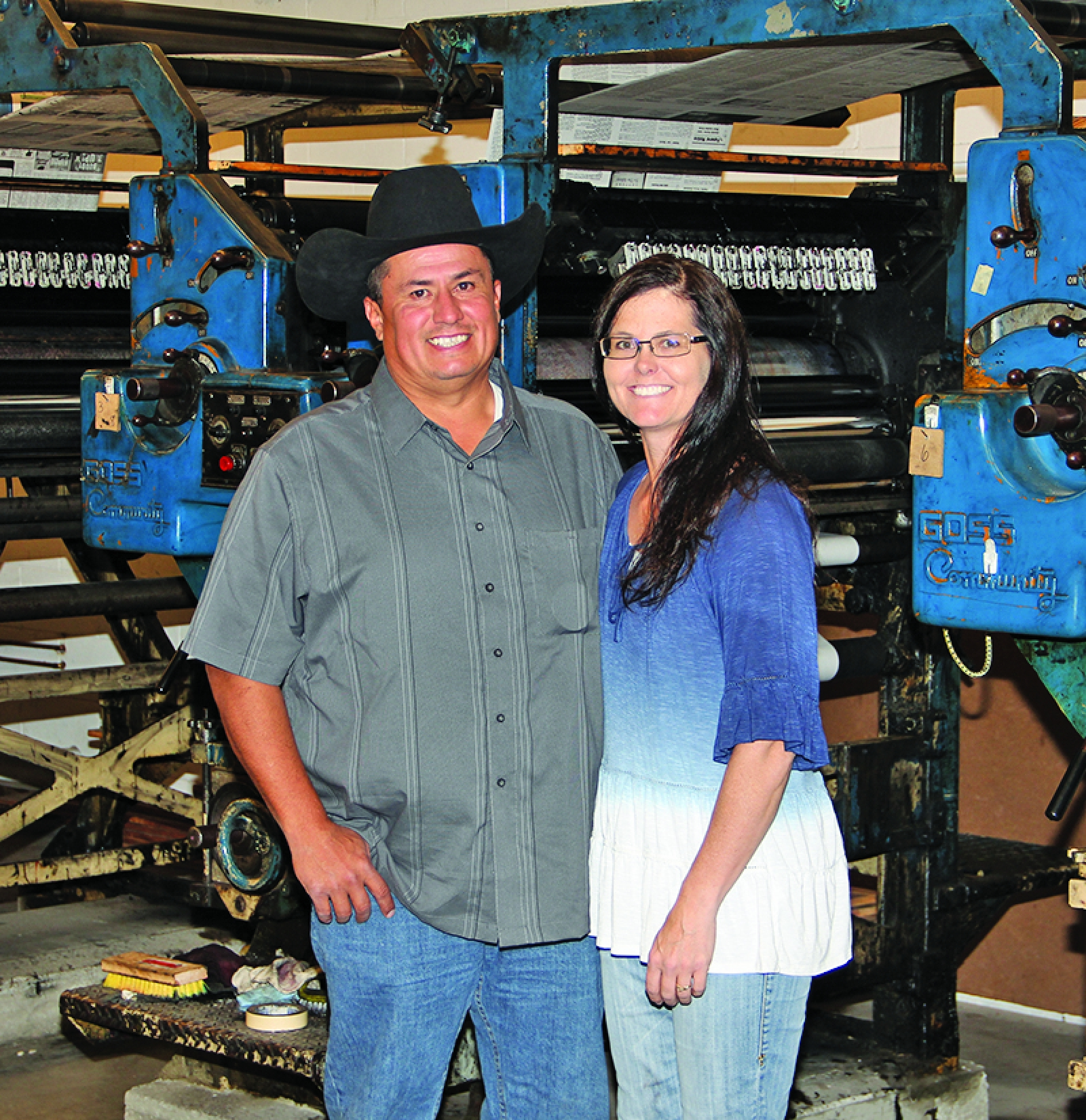 Bob and Mandy Scherer stand in front of the printing presses at the Bennett County Booster II.