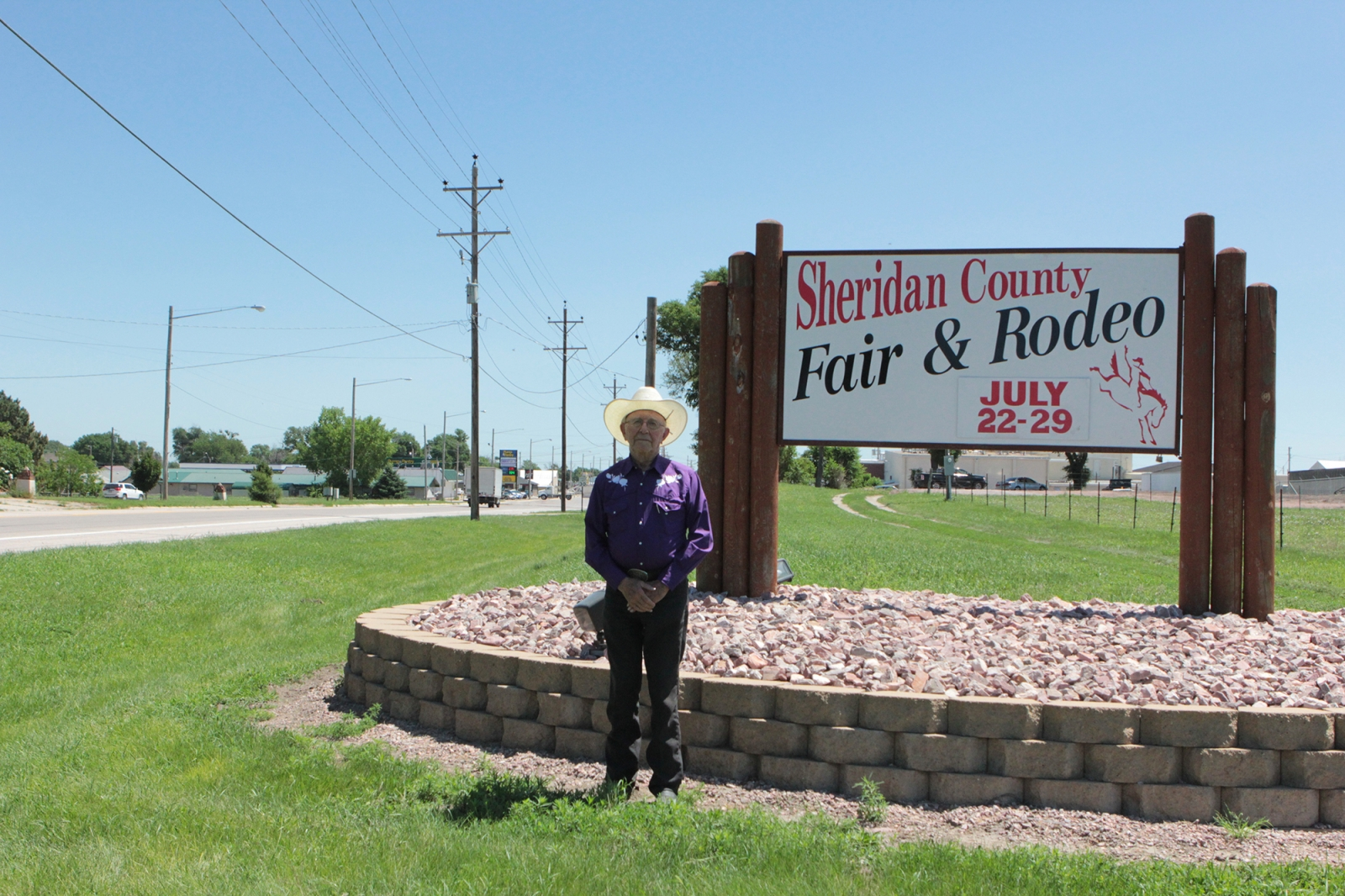 Willis Gran, the 2019 SCF&R Parade Grand Marshal, stands by a sign welcoming people to Gordon for the Fair and Rodeo events.