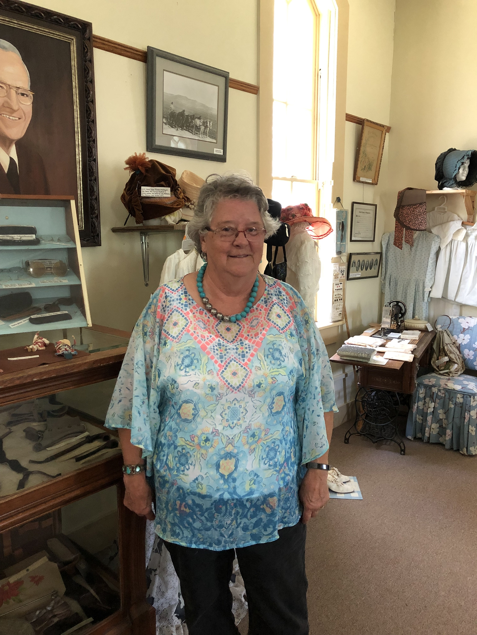 Betty Mapes stands at the Scamahorn Museum next to a hat her grandmother made. Mapes has also been volunteering with DAR to open the museum on Wednesdays for three hours throughout the summer.
