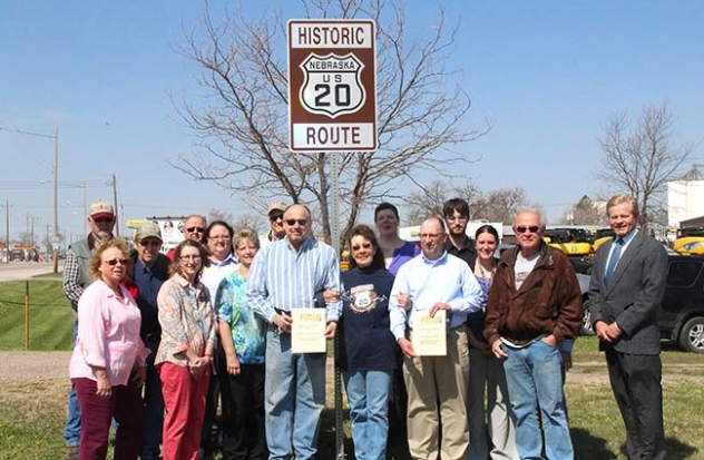 Members of the Gordon Chamber of Commerce pose by the Historic US Route 20 sign at Hamilton Park. Holding certificates are Harlen Wheeler, left, President of the Sheridan County Historical Society, and Glen Spaugh, right, of the City of Gordon. In the center is Gordon Chamber of Commerce President Bea Lou Hardin.