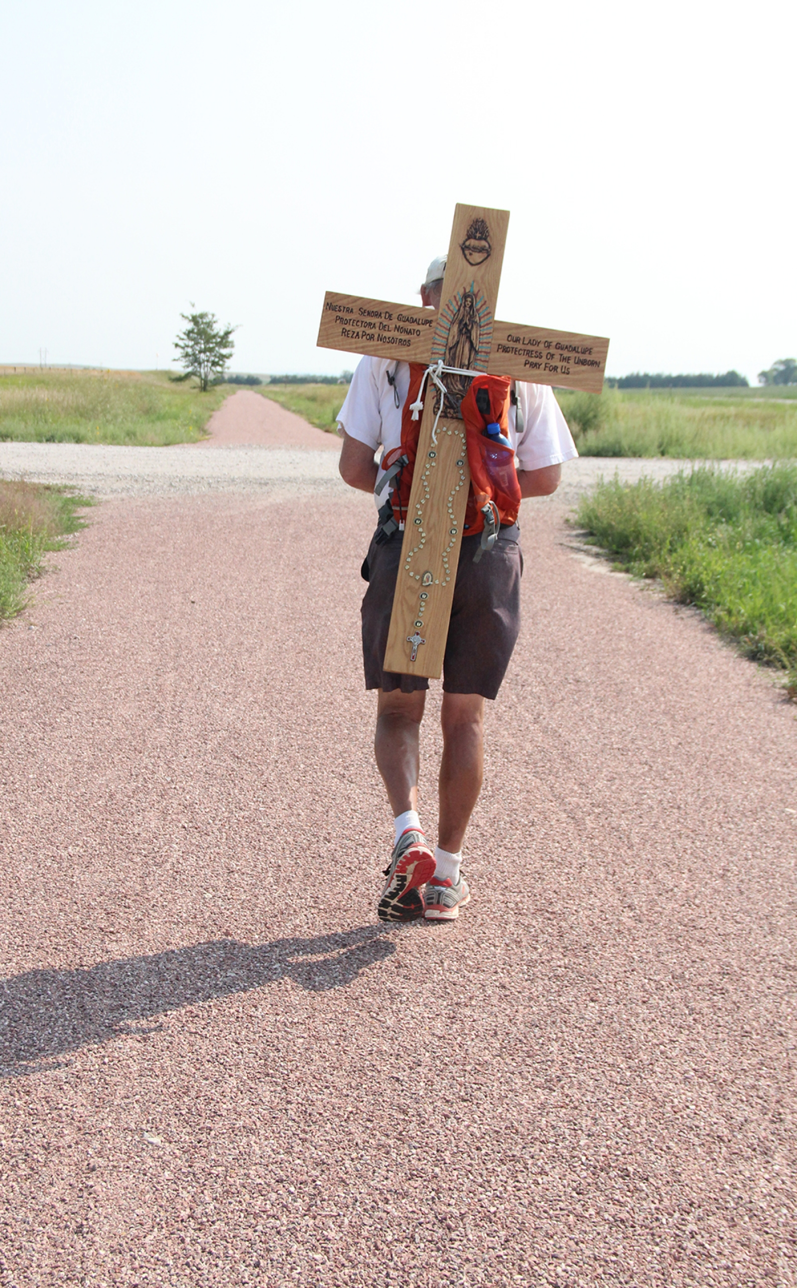 John Moore walks along the Cowboy Trail with a cross on his back. Moore is part of the way finished with his March for Life pilgrimage that ends in Washington D.C.