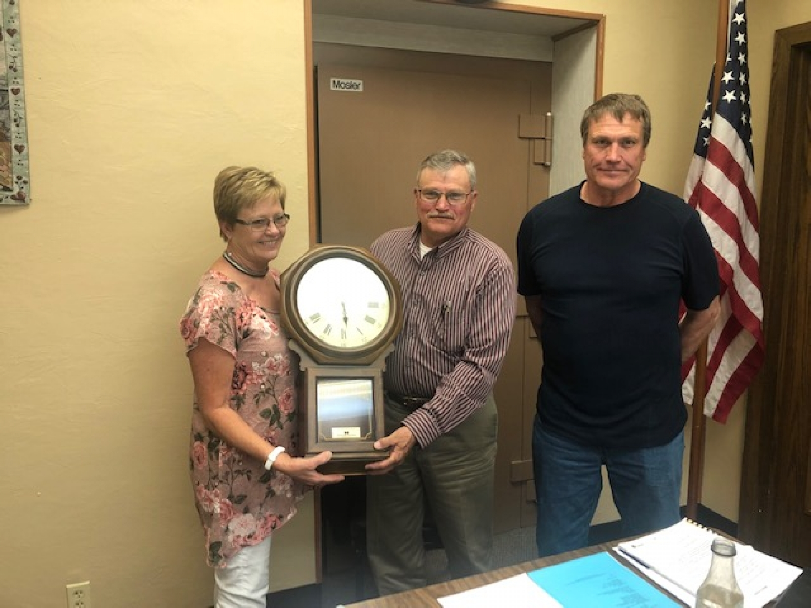 Terry Rajewich, left, and Doug Johnson, right, of NPPD present a Bulova clock to Hay Springs Mayor Richard McKay at the city council meeting on April 9.
